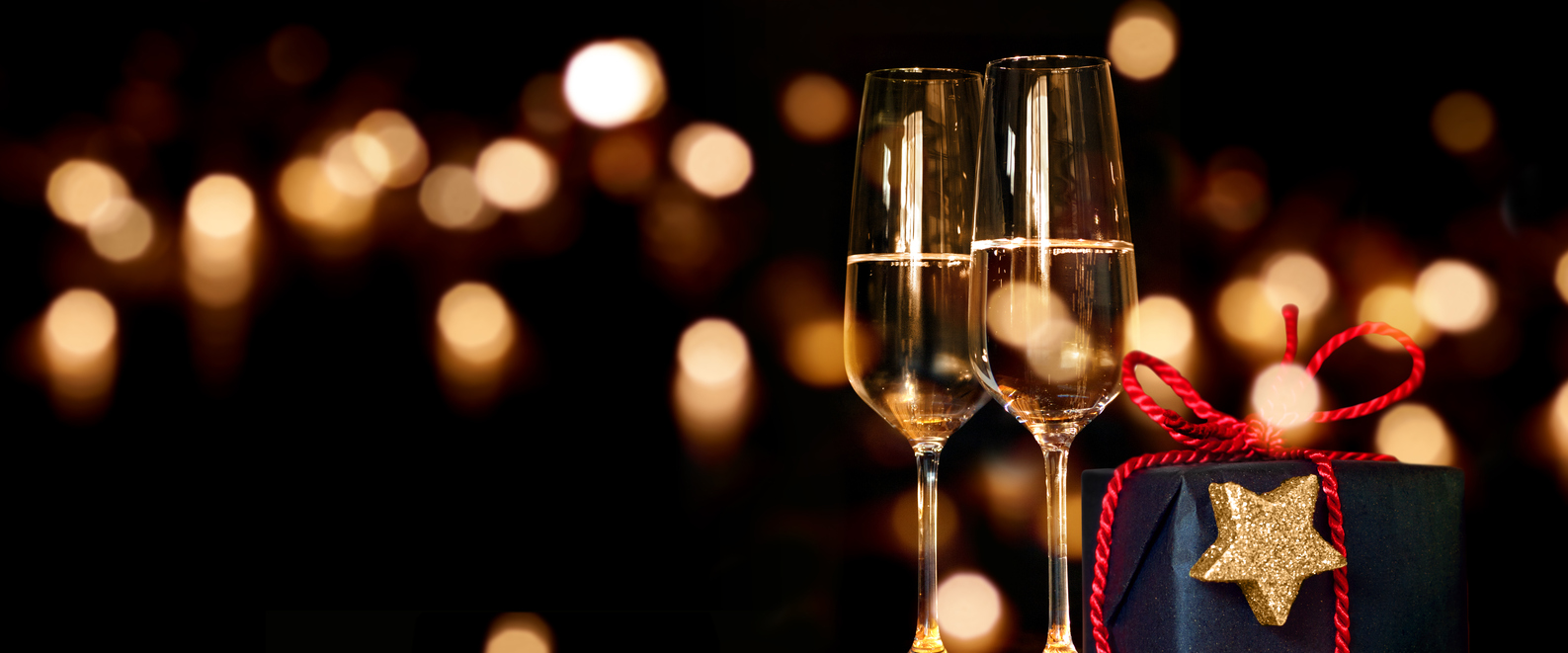 Christmas Party Venue Exeter present with champagne glasses in front of a festive lighted background